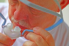 Senior puts on sleep apnea device royalty free stock image