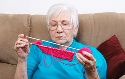 Senior putting away her knitting Stock Image