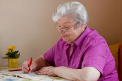 Senior puzzles with the help of reading glasses Royalty Free Stock Images