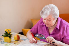 Senior puzzles with magnifying glass Royalty Free Stock Photos