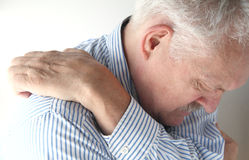 Senior reaches to scratch his back Royalty Free Stock Photography