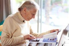 Senior reading. Senior lady reading magazine. Shallow DOF Stock Photos