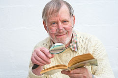 Senior reading with the aid of magnifier. A closeup image of a Senior using a magnifying lens to help him to  read a book. The image illustrates continuing Stock Photography