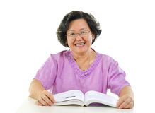 Senior reading book. Asian senior woman reading book over white background Stock Photography