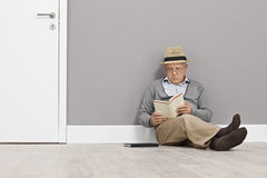Senior reading a book seated on the floor Stock Photo