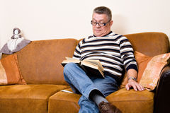 Senior reading his book on the couch Royalty Free Stock Photo