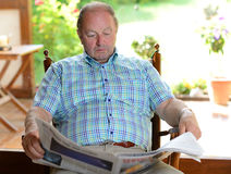 Senior is reading  newspaper Stock Images
