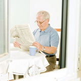 Senior reading a newspaper. Senior man reading a newspaper at home Stock Photos