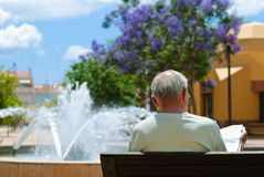 Senior Reading Newspaper. Senior male reading his newspaper on bench overlooking fountain in Silves square Stock Photos