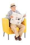 Senior reading a newspaper in a modern armchair Stock Photos