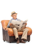 Senior reading a newspaper seated on armchair Royalty Free Stock Image
