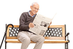 Senior reading a newspaper seated on a bench Royalty Free Stock Image