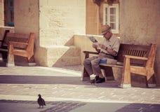 Senior reading newspaper in Valletta, Malta Royalty Free Stock Photo