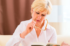 Senior reading with presbyopia book Stock Image