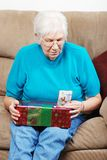 Senior reading tag on christmas present Royalty Free Stock Photo
