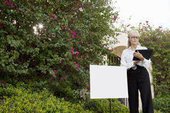 Senior real estate agent standing by sign board reading from clipboard Stock Photo
