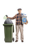 Senior with a recycling bin throwing a garbage bag. Full length portrait of a senior with a recycling bin throwing a garbage bag in a trash can  on white Royalty Free Stock Photos