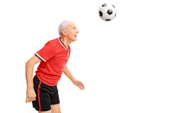 Senior in a red jersey heading a football Royalty Free Stock Photo