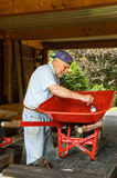 Senior  and  red wheelbarrow Royalty Free Stock Photos