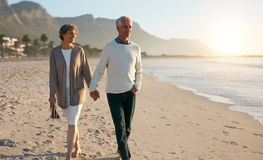 Senior relaxed couple walking on beach Stock Images