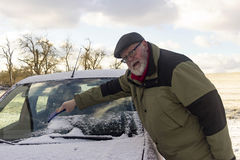 Senior remove car from hoarfrost. Outdoor Shot Royalty Free Stock Image