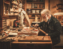 Senior restorer working with antique decor element in his workshop Stock Images