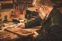 Senior restorer working with antique decor element in his workshop Royalty Free Stock Image