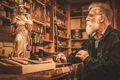 Senior restorer working with antique decor element in his workshop.  stock photos