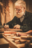 Senior restorer working with antique decor element in his workshop.  stock photography