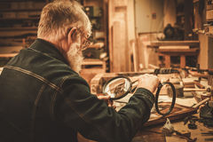 Senior restorer working with antique decor element in his workshop.  stock images