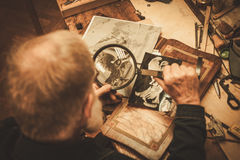 Senior restorer working with antique decor element in his workshop.  royalty free stock photography