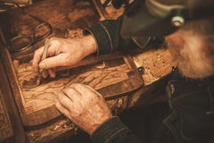 Senior restorer working with antique decor element in his workshop.  royalty free stock images