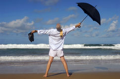 Senior retired business man, arms outstretched celebrating freedom on a tropical beach. Businessman standing on a beautiful beach with arms outstretched.  Copy Royalty Free Stock Photos