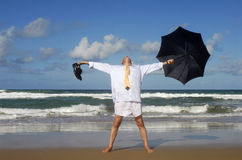 Senior retired business man arms outstretched enjoying retirement freedom on beach vacation Royalty Free Stock Images