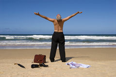 Senior retired business man sunbathing with arms outstretched on tropical caribbean beach, retirement freedom concept