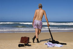 Senior retired business man undressing on caribbean beach, retirement freedom escape concept. Businessman retired and undressing on a beautiful caribbean beach Stock Photo