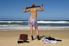 Senior retired businessman undressing and relaxing on a beach, retirement freedom concept Stock Image