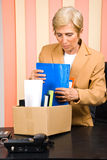 Senior retired collect her belongings in a box. Senior business woman retire and collect her belongings,check also Business people Royalty Free Stock Image