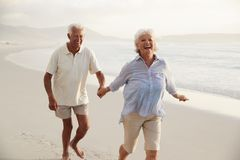 Senior Retired Couple Running Along Beach Hand In Hand Together stock images