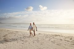 Senior Retired Couple Walking Along Beach Hand In Hand Together royalty free stock image