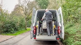 A senior retired man helping to transport disabled people stock photos