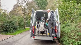 A senior retired man helping to transport disabled people royalty free stock photos