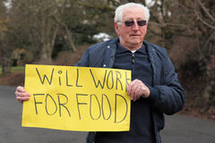 Senior retired man model with sign. Retired man with sign to work for food in this bad business economy time Royalty Free Stock Images