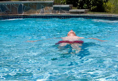 Senior retired man swimming in pool stock photography