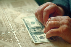 Senior retired woman with small amount of money on table, toned image, colorized, selective focus, very shallow dof Stock Photo