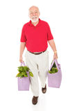 Senior with Reusable Grocery Bags. Senior man carries his groceries home in reusable cloth shopping bags. Full body isolated stock images