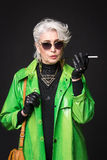 Senior rich woman. Portrait of senior rich woman in bright green coat wearing sunglasses while holding cigarette in front of her isolated on black background stock photo