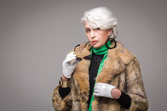 Senior rich woman. Portrait of senior rich woman holding sunglasses in front of her. Vogue lady in fur coat posing in studio  on grey background Stock Photos