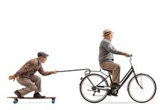 Senior riding a bike with another senior riding a longboard and Royalty Free Stock Images