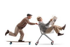 Senior riding a longboard and pushing a shopping cart with another senior riding inside it and holding a newspaper stock photos